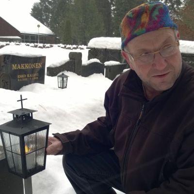 Savonlinnan seurakunnan ylipuutarhuri Pasi Inkinen esittelee led-kynttilää Talvisalon hautausmaalla joulukuussa 2017.