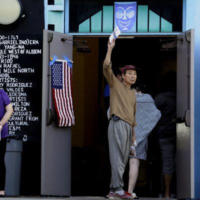 Kätensä kohottanut äänestäjä jonottaa vaalihuoneiston ovella. Oveen on teipattu Yhdysvaltain lippu ja oven päällä on naurava naamio.