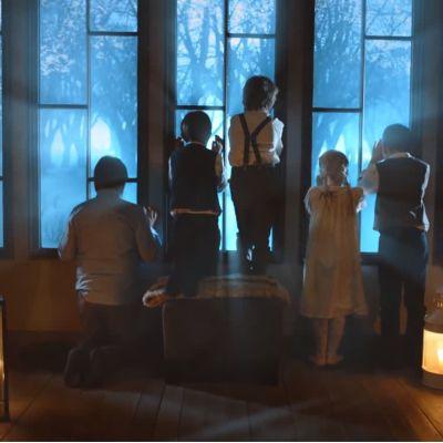 Viisi lasta tähyilee ikkunasta ulos kynttilänvalossa.
