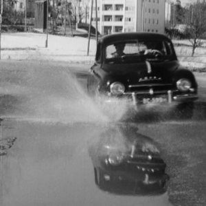 Auto roiskuttaa vettä keväisellä kadulla.