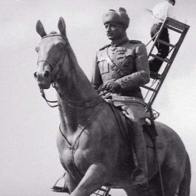 Mies telineillä Marskin patsaalla (1960)