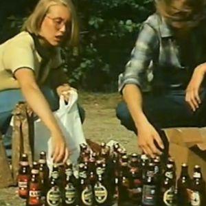 Kaksi nuorta ihmistä ja olutpulloja.