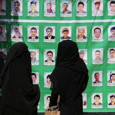 Kuvassa kolme peittävään niqabiin pukeutunutta huthi-naista katselee marttyyrien muotokuvia Jemenissä helmikuun lopulla vuosittaisen Marttyyrien päivän kunniaksi järjestetyssä näyttelyssä.