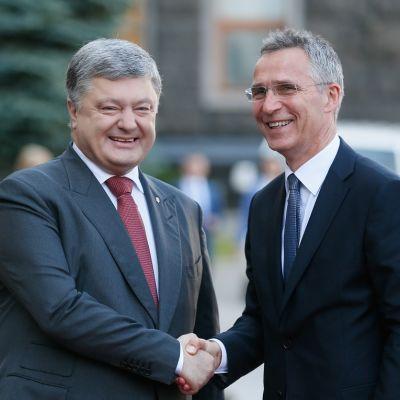 Kuvassa Ukrainan presidentti Petro Poroshenko vasemmalla ja Jens Stoltenberg oikealla. He kättelevät ja hymyilevät.