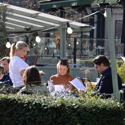 Seurua ravintolan terrassilla, tarjoilija ottamassa tilauksia.