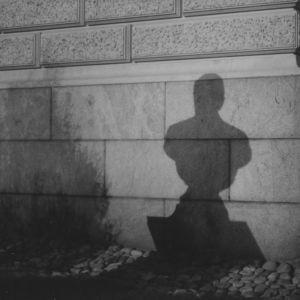 Patsaan varjo heijastuu Säätytalon seinään pimeässä Helsingissä.