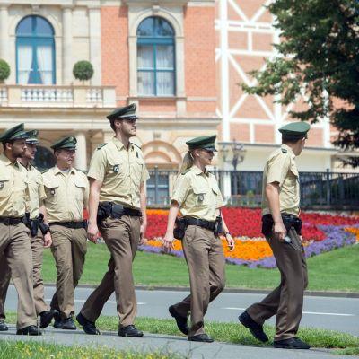 Seitsemän poliisia marssii Bayreuthin oopperajuhla-alueella.