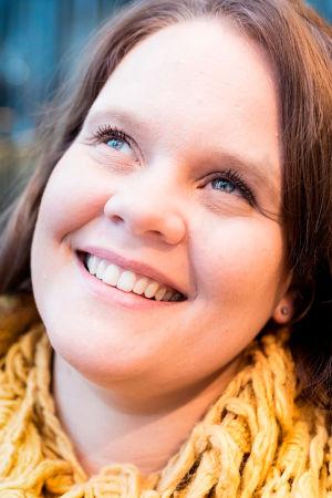 Aleksandra Mirolybov-Nurmela hymyilee kuvassa ja katsoo yläviistoon. Kuvan vasemmassa yläreunassa valkoinen Vaakakapina-leima.