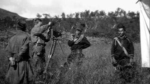 """Rasundersökare i arbete i trakten av Gällivare sommaren 1925. En av bilderna i ett privat fotoalbum som finns på museet Ájtte i Jokkmokk. På bilderna kan man se hur de utsända """"rasundersökarna"""" kommer vandrande och förväntar sig att bli mottagna som gäste"""