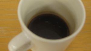 Lähikuva kahvikupista, jossa on mustaa kahvia.