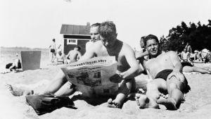 Tre män sitter på stranden. En läser tidningen.