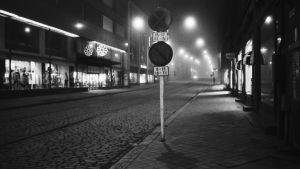 Svartvit bild på alldeles öde gata på natten med gatubelysning.