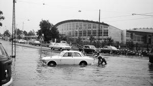 Veteen juuttunutta autoa työnnetään tulvivalla Nordenskiöldinkadulla
