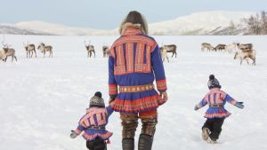 Pappa och två pojkar i samedräkt  i snö med renar