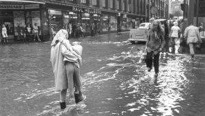 Äiti kantaa lapsen tulvivan kadun yli Helsingissä v. 1974