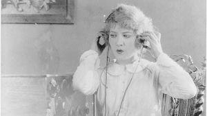 Kvinna lyssnar på radio med hörlurar.
