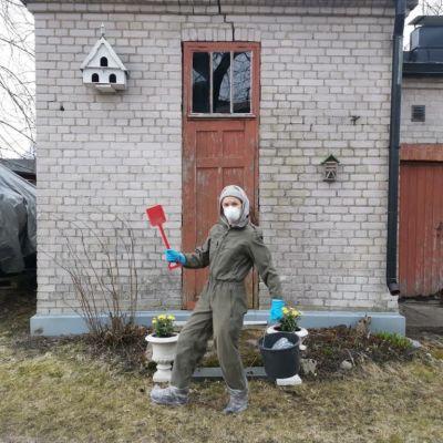 kvinna i mask och spade framför byggnad