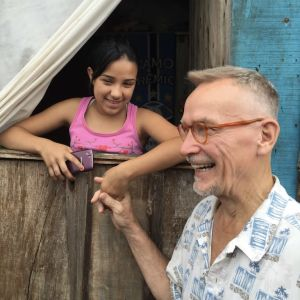 Perrti Simula pitää kädestä pikkutyttöä, taustalla hökkelimäinen rakennus Brasiliassa.