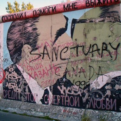 Graffititäckt bild på Brezjnevs och Honeckers broderskyss på Berlinmuren