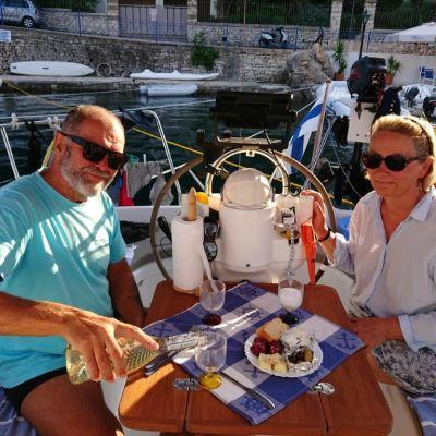 en vkinna och en man dricker vin i sittbrunnen i en segelbåt