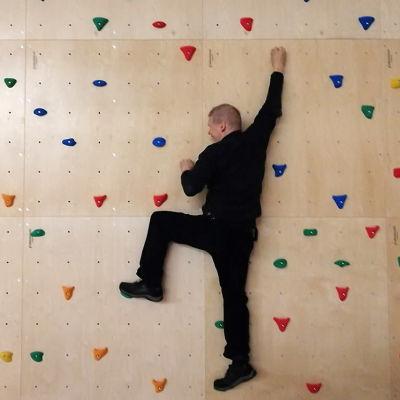 Mies kiipeilee liikuntahallin seinällä.