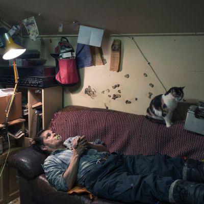 """Kainuulainen mies, """"Tutti-Tuomas"""", makaa sohvalla ja imee tuttia."""