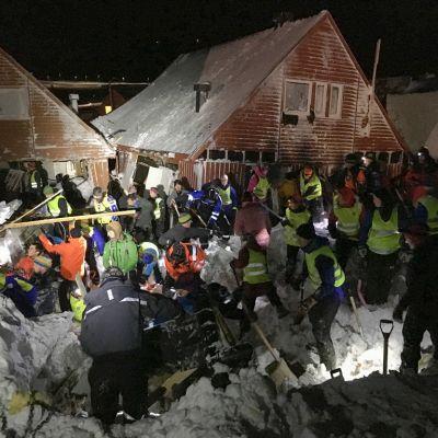Pelastushenkilöstö etsii lumivyöryn uhreja vyöryn osittain hautaamien talojen vierellä.