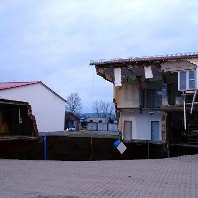 Maanvajoama reunoilla on kaksi rakennusta, joista osa on sortunut kuoppaan.