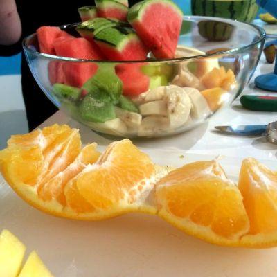 Kuorittu appelsiini laudalla ja pilkottuja hedelmiä vadissa.