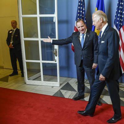 Stefan Löfven ohjaa kädellään Joe Bidenia kohti ovea. Biden ottaa askelta kohti ovea. Molemmilla on tummansiniset puvut ja erilaiset siniset kravatit. Miehet hymyilevät. Seinällä taustalla on Yhdysvaltain ja Ruotsin lippuja. Oven takana seisoo turvamies mustassa puvussa.