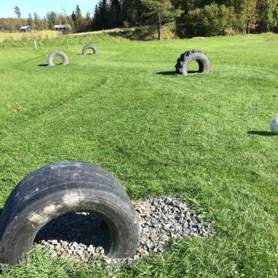 Vanhat traktorin renkaat on upotettu jalkapallokenttään uudentyyppisen golfradan tehtäväradalla. Golfia pelataan jalkapalloa potkimalla.