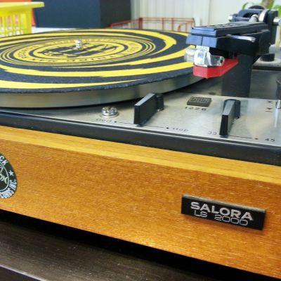 Värikäs lp-levy asetettuna puukoteloisen levysoittimen päälle.
