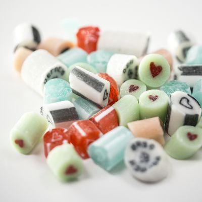 Erivärisiä karkkeja, joissa on sydämenmuotoisia kuvioita.