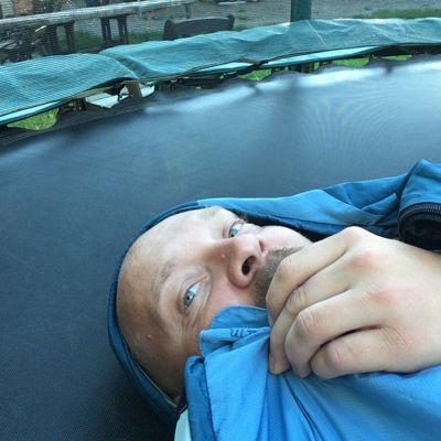 Toimittaja kurkistaa makuupussista maatessaan trampoliinilla.