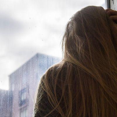 Tyttö katsoo ikkunasta ulos.