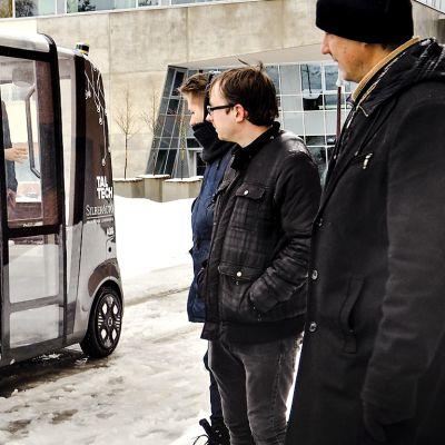 Miehet katselevat itseohjautuvaa Iseautoa, joka on pysähtynyt lumiselle kadulle.