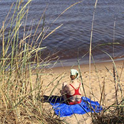 Nainen istuu uimarannalla.