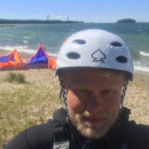 Niko Karstikko i våtdräkt med en vit hjälm på huvudet på en strand i Hangö.