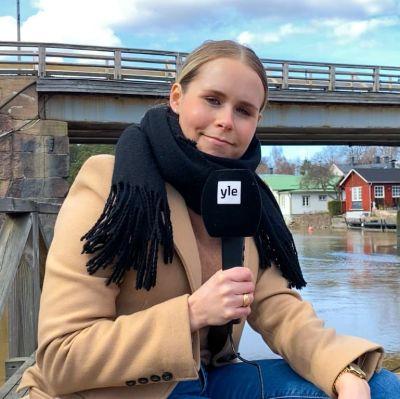 En kvinna som ler och sitter på en bänk nedanför en bro.