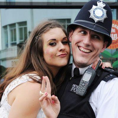 Nuori nainen halaa nauravaa poliisia ja näyttää voitonmerkkiä.