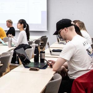 Studerande sitter i ett klassrum, en lärare står framför och föreläser.