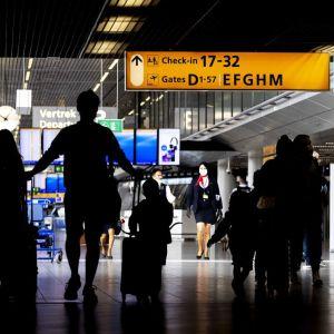 En mans siluett drar på reseväskor på flygplatsen .