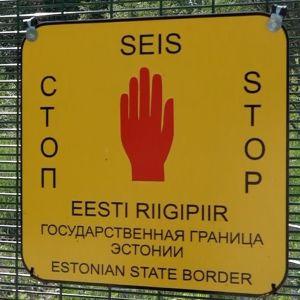 En skylt som säger stop här går Estlands gräns mot Ryssland på ett gränsstaket