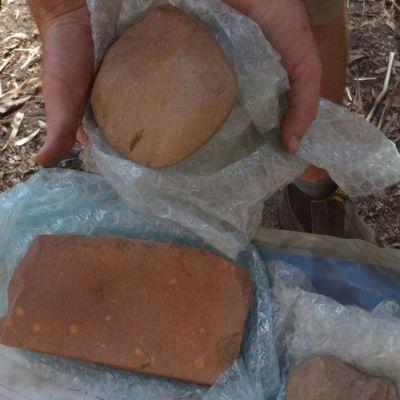Tutkija pitelee käsissään yhtä kivikirvestä, edessä hiomakivi.