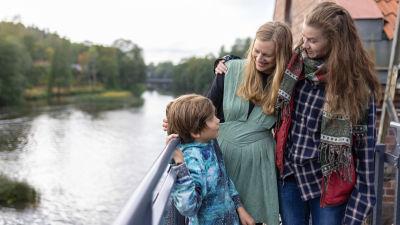 Två kvinnor står nära varandra tillsammans med en pojke. De står vid en å.