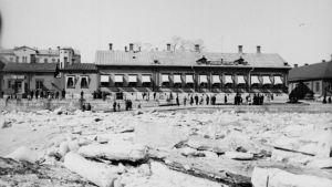 Islossning i Aura å.Tiotals människor skådar Halisgubbarna vid Västra Strandgatan 17.