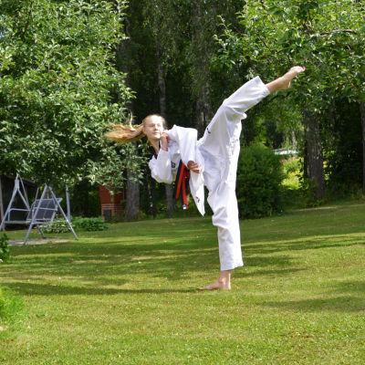 En ung kvinna i taekwondodräkt sparkar upp i luften. Hon står på en gräsmatta framför några äppelträd.