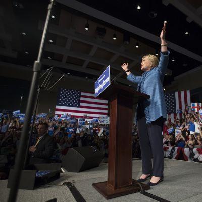 Hillary Clinton kädet koholla puhujapöntössä. Ympärillä Yhdysvaltain lippuja ja kampanjajulisteita heiluttelevia ihmisiä.