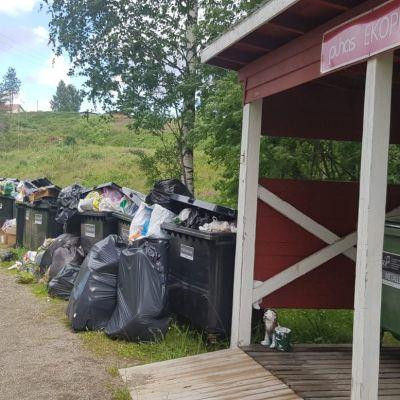 Ilomantsin Hattuvaarassa sijaitseva jätekeräyspiste, jonka astiat ovat ääriään myöten täynnä. Myös maahan on jätetty roskia.