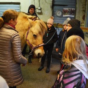 Flera barn står runt en beige häst. De lyssnar på en kvinna och en man som talar.